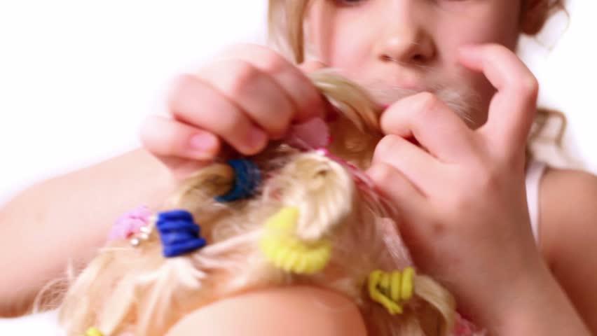 Little girl use elastic band to braid dolls hair, closeup view | Shutterstock HD Video #1999175