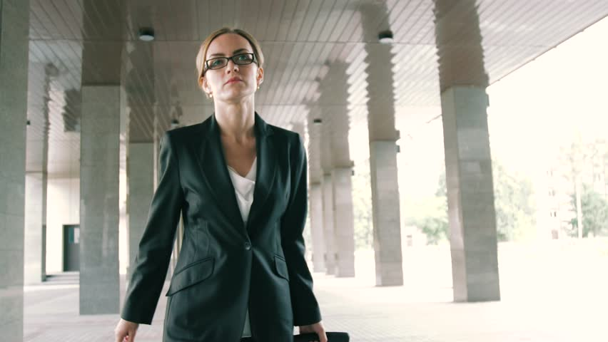Close-up of a confident blond businesswoman walking with trolley in the urban environment   Shutterstock HD Video #19998682