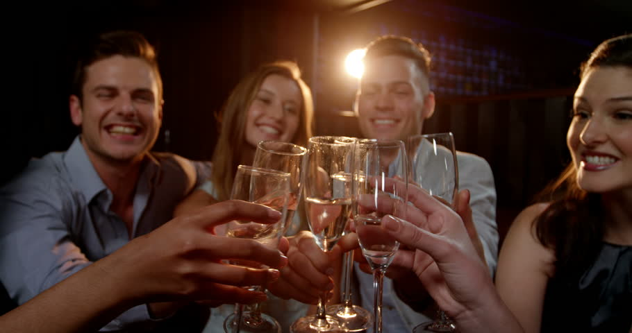 Group of smiling friends sitting on sofa and toasting a glasses of champagne at bar 4k | Shutterstock HD Video #20013562