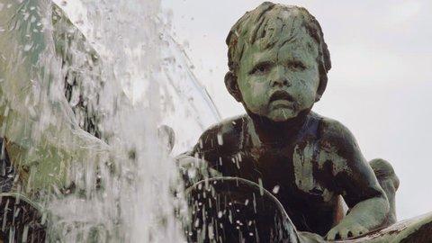 Boy Sculpture Behind Water. Detail Of The Neptune Fountain In Berlin