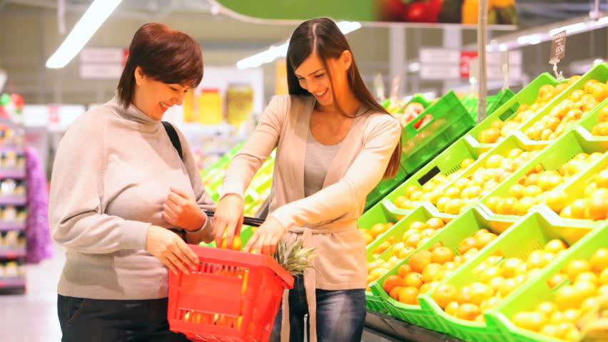 Mother and daughter choosing ripe oranges and putting them into a market basket   Shutterstock HD Video #2005157