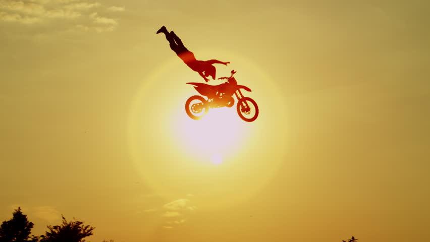 SLOW MOTION SILHOUETTE: Pro motocross rider riding fmx motorbike, jumping big air kicker performing extreme stunt. Professional biker jumps no hander superman trick over orange sunset sky