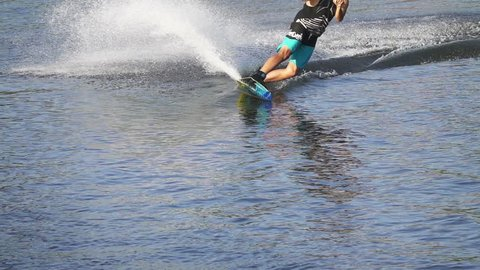 Kiev, Kyiv, 4 September 2016, Wakeboarder man rides a wakeboard in turquoise shorts, slow motion
