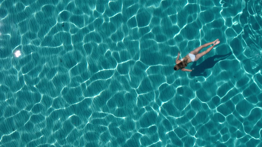 Aerial - Beautiful young woman with toned body swimming underwater in crystal clear water | Shutterstock HD Video #20106637