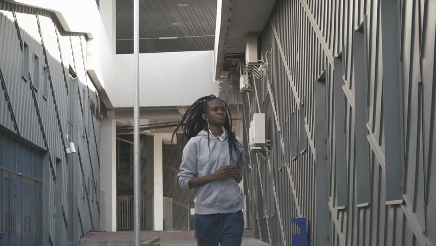 Young woman running and listening to music in an urban street | Shutterstock HD Video #20109457