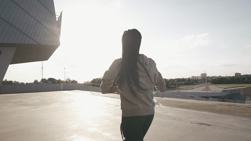 Silhouette of girl walking through the street and dancing