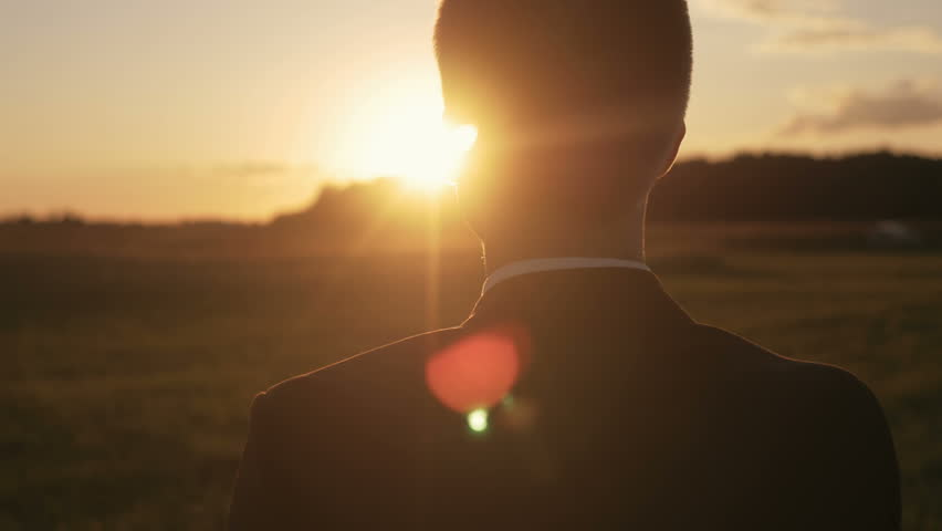 Young man looking forward at the sun during the sunrise. Businessman thinking about business planning.   Shutterstock HD Video #20127235