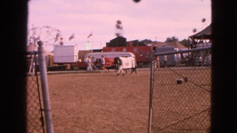 DEVILS LAKE, WISCONSIN 1963: horses being guided through a lot with an amusement park in the background