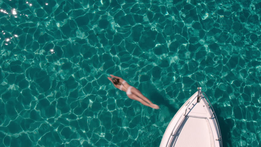 Aerial - Top view of a beautiful young woman jumping from a motor boat bow into crystal clear transparent water of a luxury travel destination