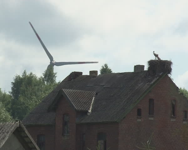 windmill spins and stork nest on abandoned rural building. Alternative wind energy generation.
