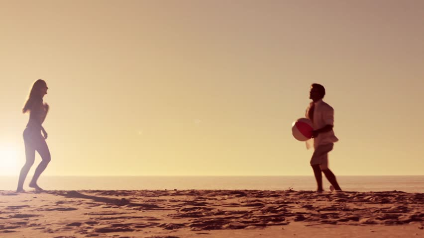 Couple playing with a beach ball on the beach at sunset. vacation healthy lifestyle clip