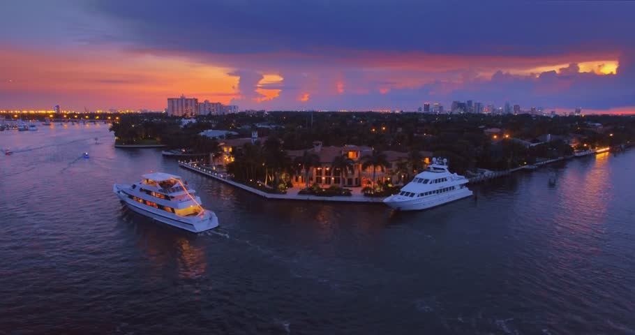 Miami cityscape at sunset, yachts and boats commuting on river. Hollywood, Miami, Florida, 4K UHD aerial view.