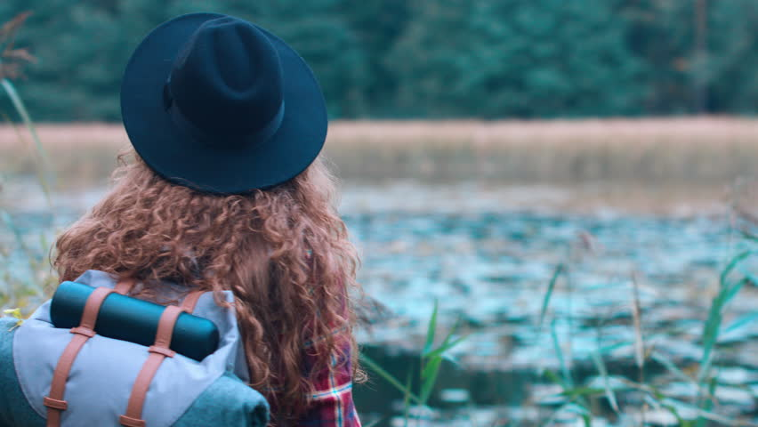 Active healthy Caucasian woman with a backpack taking pictures with an vintage film camera on a forest lake. 4K UHD RAW edited footage