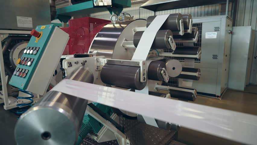 Massive, high-tech equipment at the enterprise. Manufacturer of films for the sausages. A wide, metal spinning shafts.    Shutterstock HD Video #20182036
