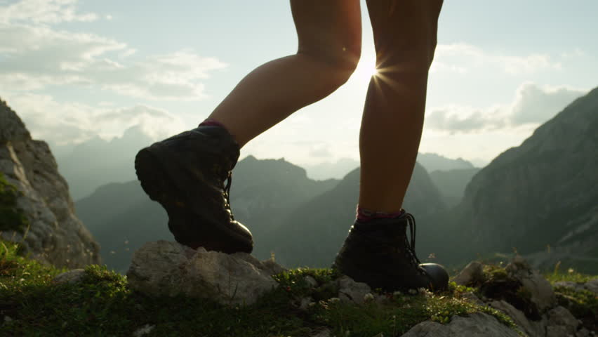 SLOW MOTION, CLOSE UP: Unrecognizable courageous female hiker climbing mountaintop, walking off trail on dangerous rocky mountain ridge. Steep wall opening beautiful view on high European Alps