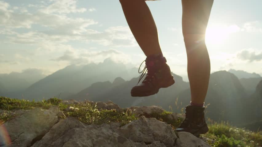 SLOW MOTION, CLOSE UP: Courageous female hiker climbing mountaintop, walking off trail on dangerous rough rocky mountain ridge. Steep wall opening beautiful view on high European Alps sunbathing #20183839