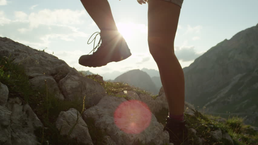 SLOW MOTION, CLOSE UP: Courageous female hiker climbing mountaintop, walking off trail on dangerous rough rocky mountain ledge. Steep wall opening beautiful view on high European Alps sunbathing #20183842