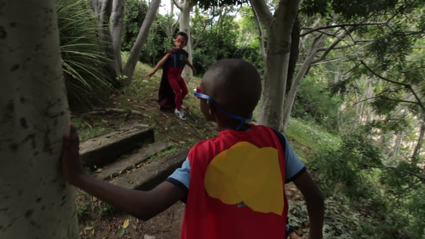 Two young boys dressed in homemade superhero costumes run down the walkway in their backyard garden, jumping several stairs at a time. Slow motion.