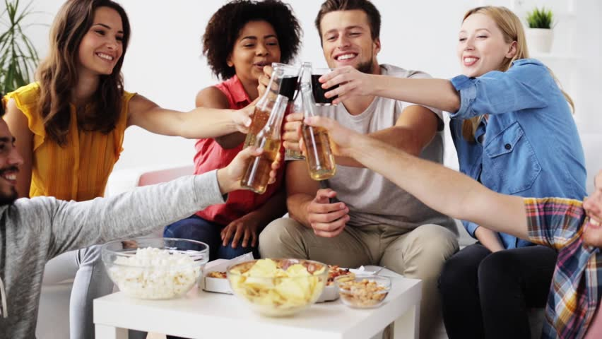 friendship, leisure, fast food, unhealthy eating and celebration concept - happy friends with drinks and snacks clinking bottles at home #20198125