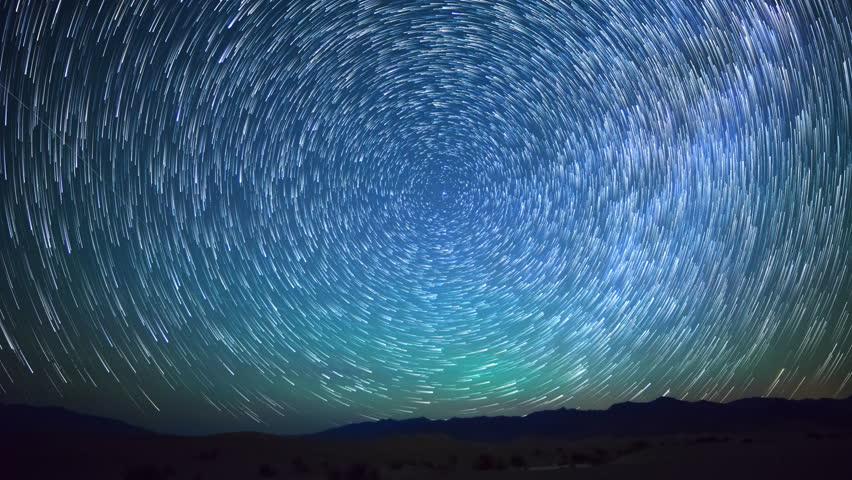 Astrophotography time lapse with pan right motion of star trails over sand dunes in Death Valley National Park, California