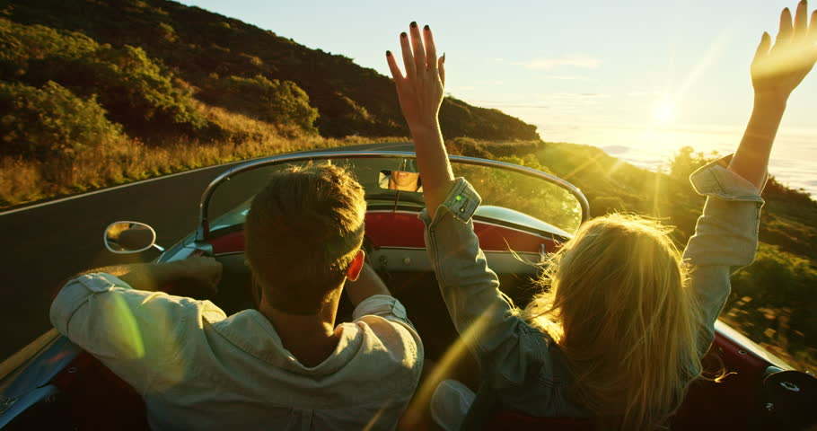 Happy couple driving on country road into the sunset in classic vintage sports car #20219089
