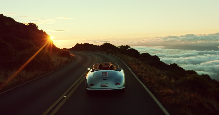 Happy couple driving on country road into the sunset in classic vintage sports car #20220283