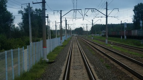 Train passing through countryside, moving railroad tracks in day