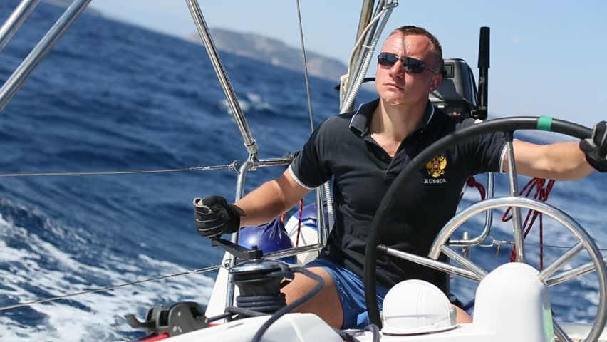 Russian skipper at the helm controls of a sailing yacht during race.