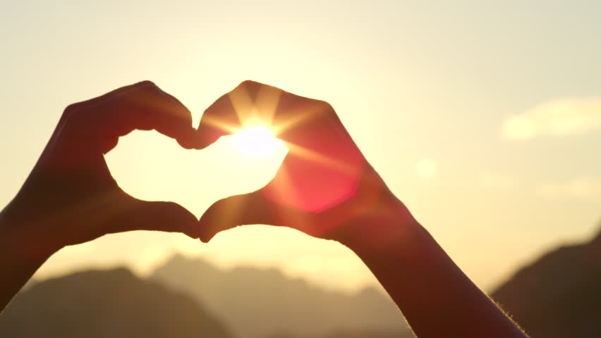 SLOW MOTION, CLOSE UP: Unrecognizable woman catching setting sun with her heart shaped fingers. Young girl making the symbol of love with her hands against stunning golden sky and rising morning sun