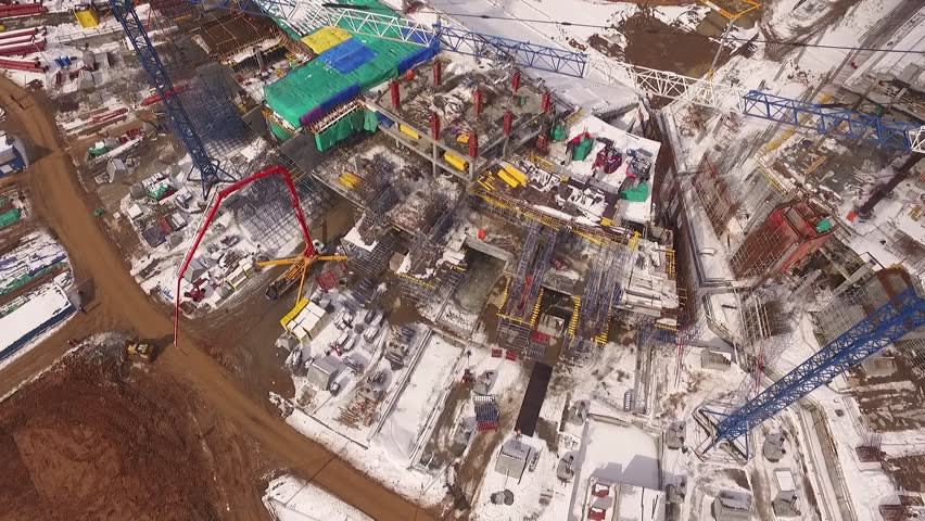drone flying over boom of huge construction crane on stadium building in winter time #20242678