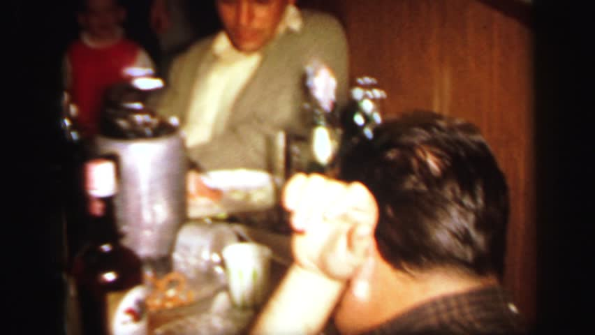 LYNBROOK, NEW YORK 1972: people gathered around a table preparing to eat a birthday cake   Shutterstock HD Video #20258095