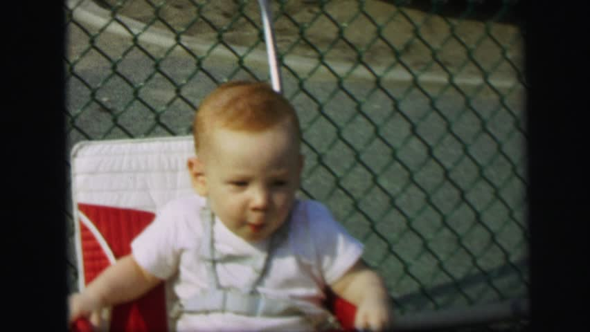 LYNBROOK, NEW YORK 1972: excited toddler trying to escape baby seat.