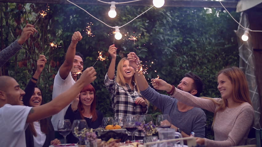 Friends holding lit sparklers at a dinner party