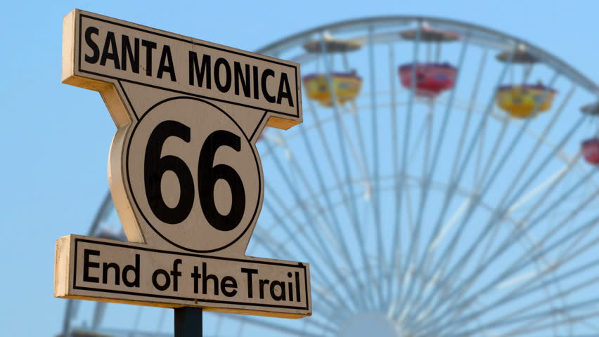 End of the Route 66 trail sign with the Santa Monica Pier Ferris wheel in the background