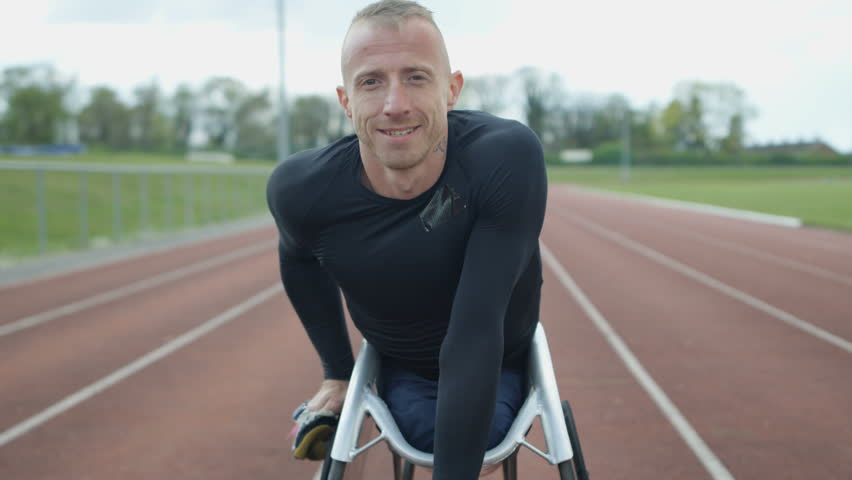 4K Portrait of smiling disabled athlete in specialist wheelchair at racing track