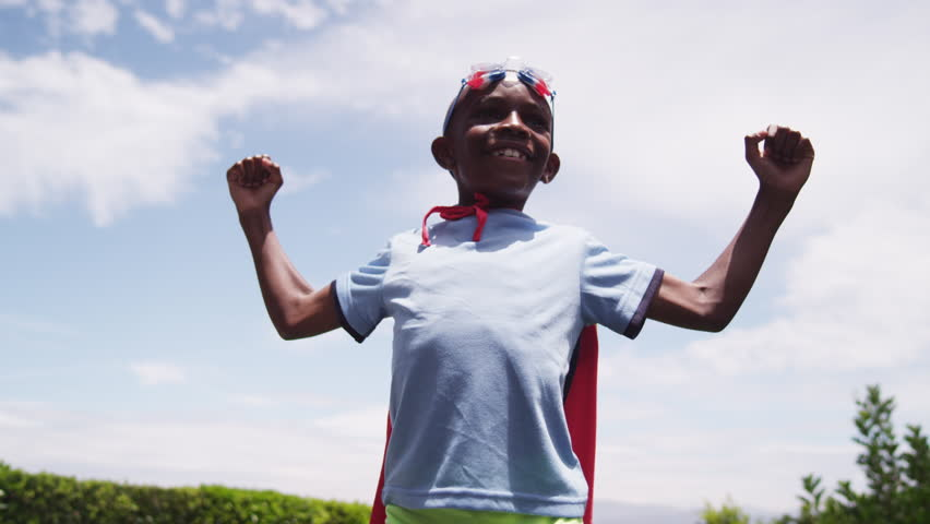 A young boy dressed in a homemade superhero costume raises his arms like a comic book hero. A golden light shines across him as he smiles. Bright, blue sky in the background. Low angle. Slow motion.