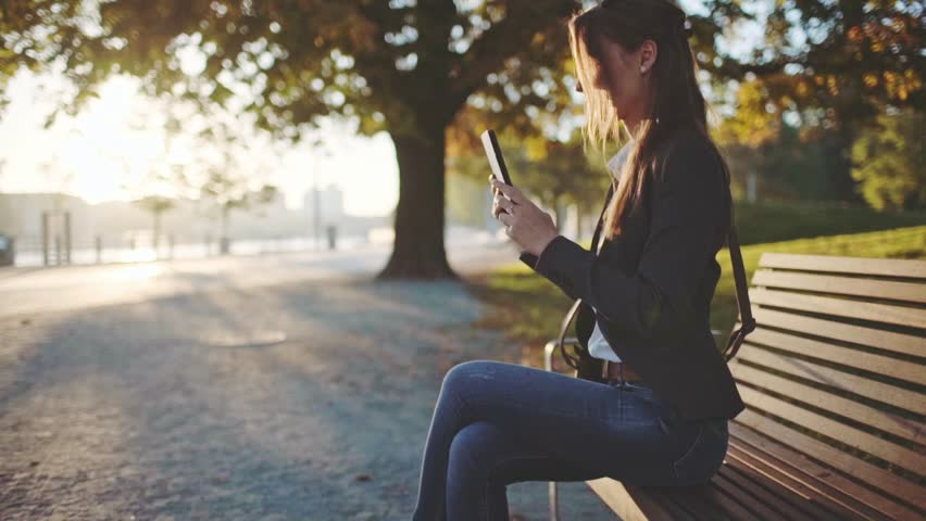 Young Businesswoman Using Digital Tablet, Sitting on the Bench in the Park in the Sunny Morning City. SLOW MOTION. STEADICAM Stabilized Shot. Business Woman Relaxing Outdoors. Lens Flare. | Shutterstock HD Video #20312170