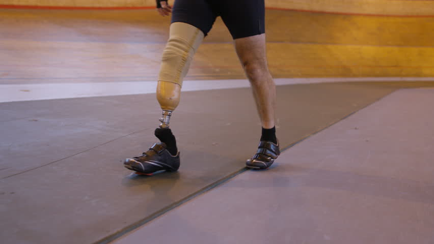 4K Unrecognisable competitive cyclist with prosthetic leg, preparing to train in velodrome. Shot on RED Epic.