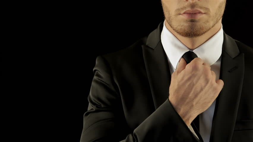 Caucasian male model in stylish black suite corrects his necktie.
