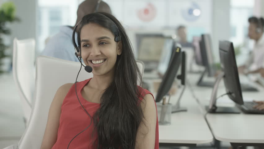 4K Friendly customer service operator taking calls in busy call centre. Shot on RED Epic.