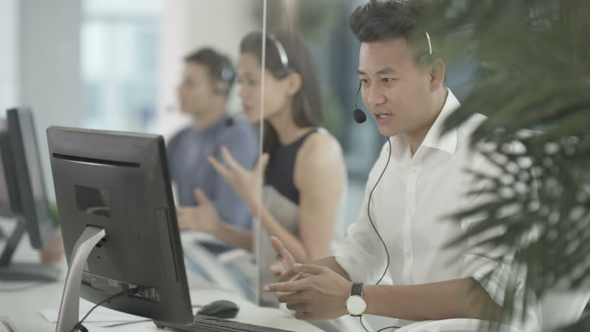 4K Friendly mixed ethnicity telesales team taking calls in busy call centre. Shot on RED Epic.