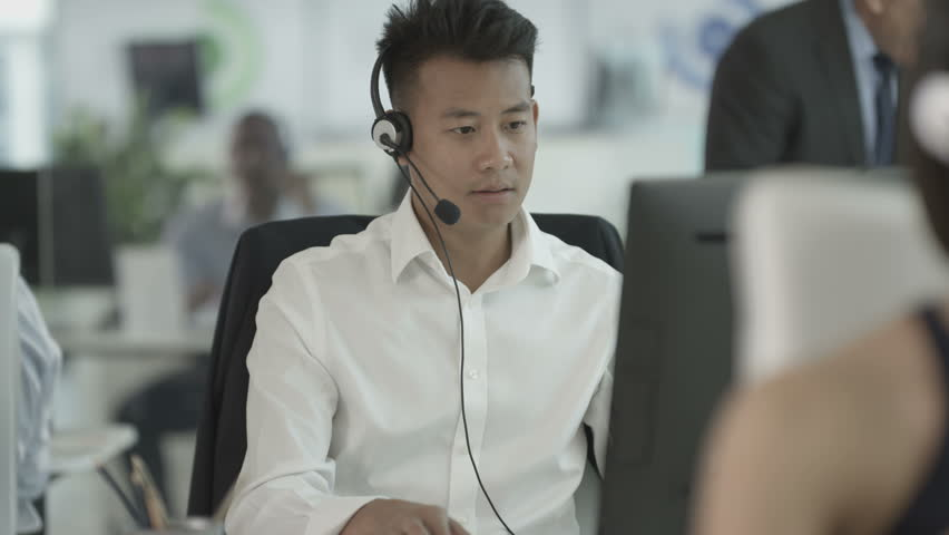 4K Friendly customer service operator with headset talking to customer in busy call centre. Shot on RED Epic. | Shutterstock HD Video #20343664