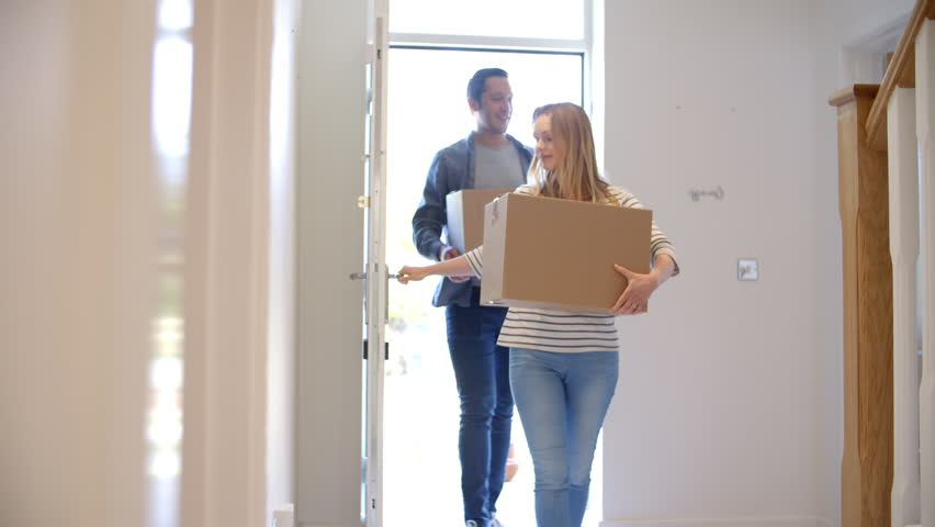 Couple Carrying Boxes Into New Home On Moving Day #20365333
