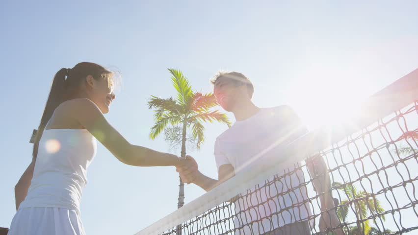 Tennis players handshake thanking each other for a game of tennis on court outdoor. Couple or mixed double tennis partners after playing tennis outside in summer. Happy young people, woman and man. Royalty-Free Stock Footage #20386843
