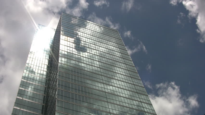 A tall mirrored skyscraper reflects the clouds going by in a timelapse shot.