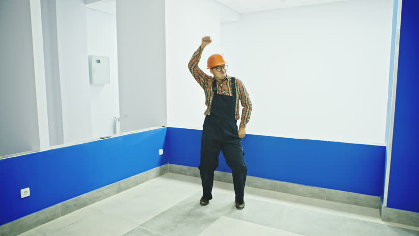 Single construction worker in room dancing fun