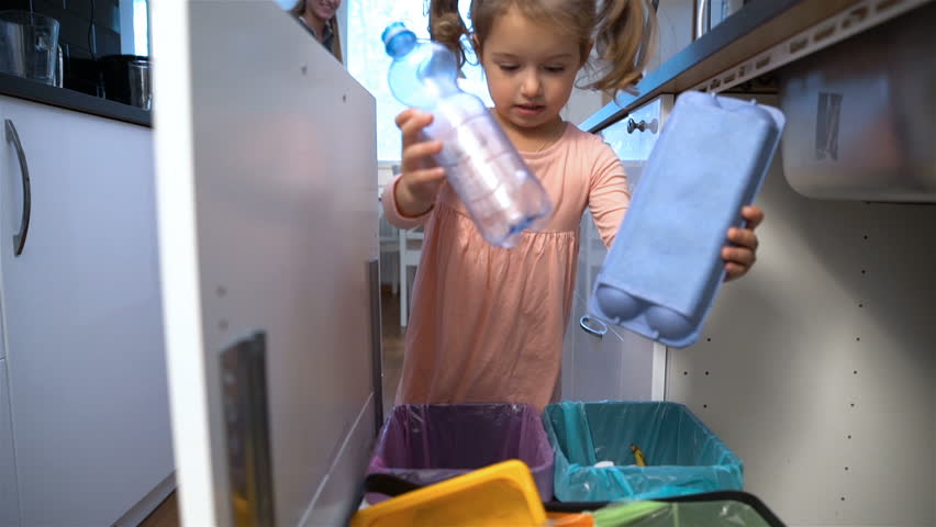 Little girl drops the trash into kitchen recycling bin. Slow motion. #20439763