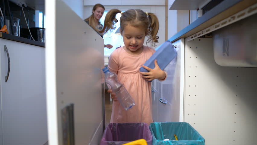 Little girl drops the trash into kitchen recycling bin. #20439769