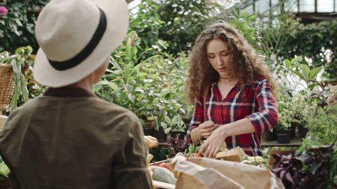 Young woman choosing vegetables at farmers market, paying for them and then taking paper bag and walking away