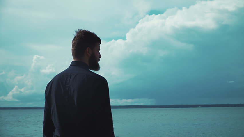 Young stylish man with a beard smokes an electronic cigarette in the background of the sea and clouds epic. Modern fashion vaping #20455072